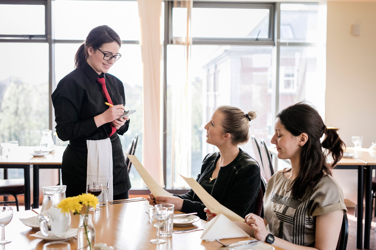 Hospitality student taking an order in the student restaurant