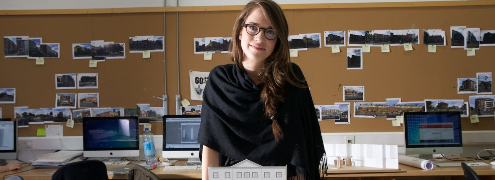 A female architecture student stands smiling behind a model of her work