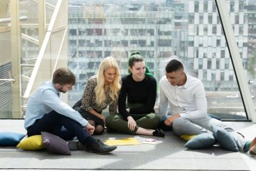 Four students sitting together on the floor working on a project