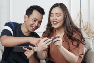 A man and woman sitting on a couch inside, looking at a phone screen together
