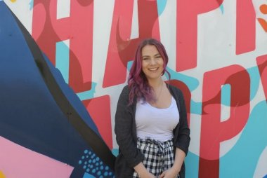 """Marisa Layes standing in front of the """"Happy"""" mural at Griffith College Dublin"""
