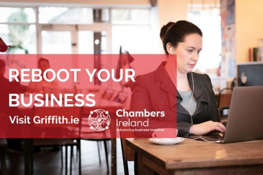 A woman using her laptop at a table to access the Chambers Ireland and Griffith College business planning course