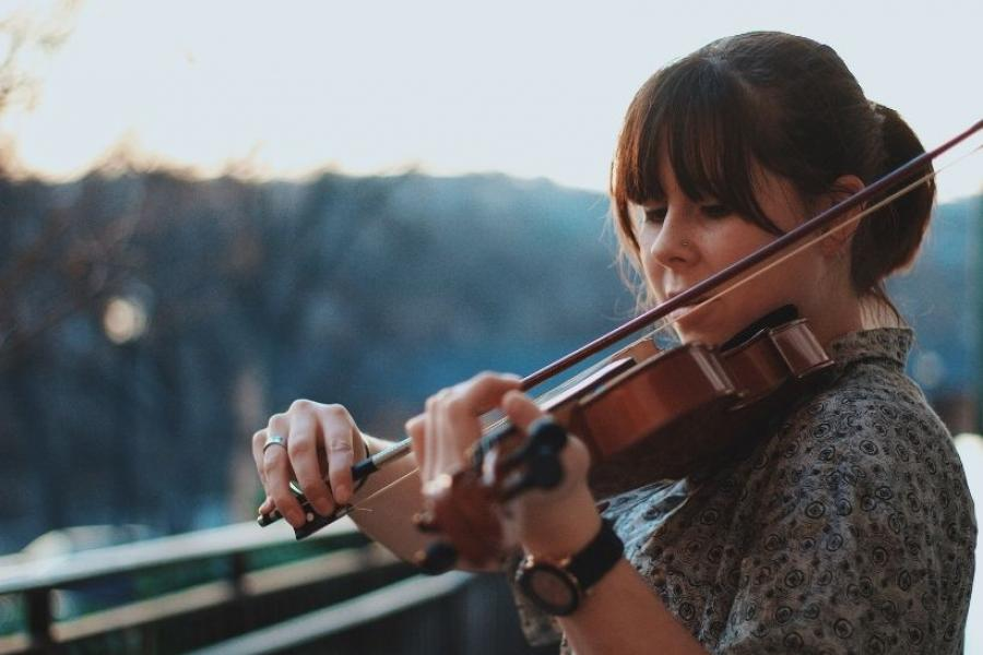 A young woman playing violin on a balcony with trees in the background