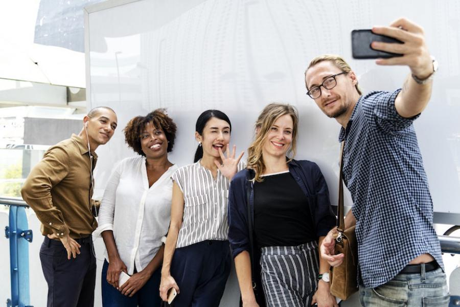 A smiling group recording a video on a phone