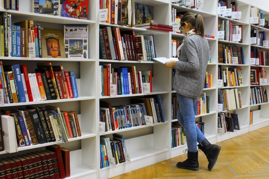 A postgraduate student browsing shelves in a library