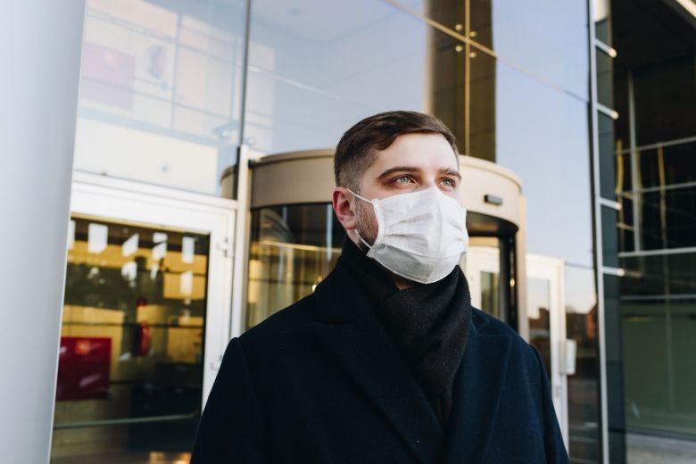 A man wearing a mask outside a building