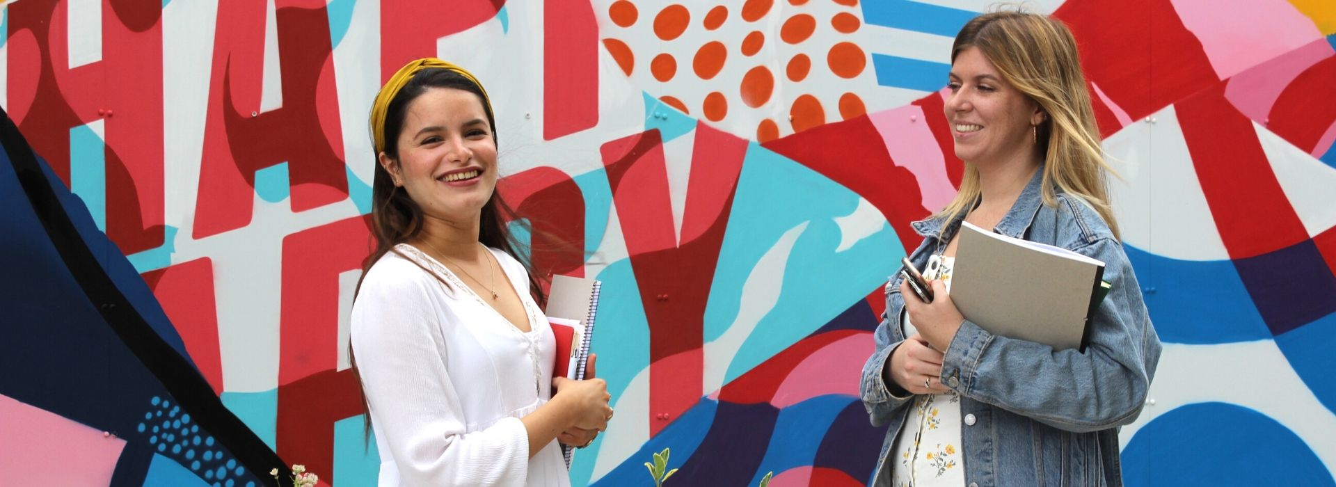 "Two young female students in front of the ""Happy"" mural on Griffith College Dublin's campus."