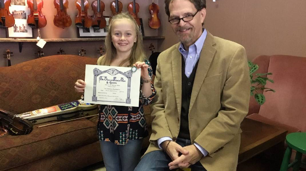 Abi Snell in 2019 with her music teacher and her Level 3 Certificate