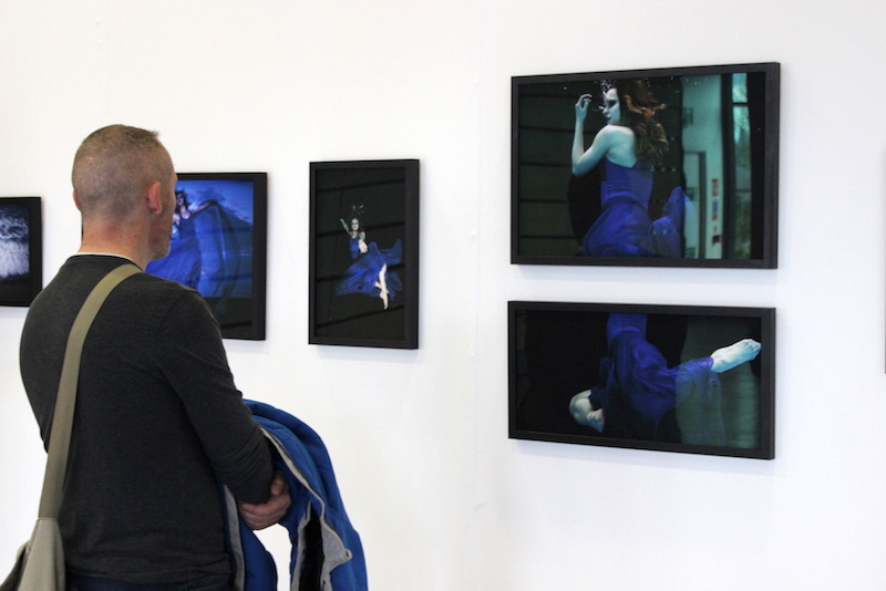 A man views one of the photography collections at the Griffith College Creative Show