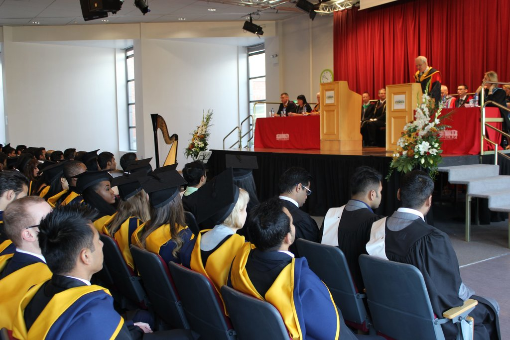 Several rows of graduates in cap & gowns look up at a raised dais with a speaker at a Griffith College graduation ceremony