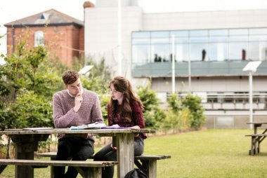 Students sitting at a picnic table on the grass at Griffith College Dublin