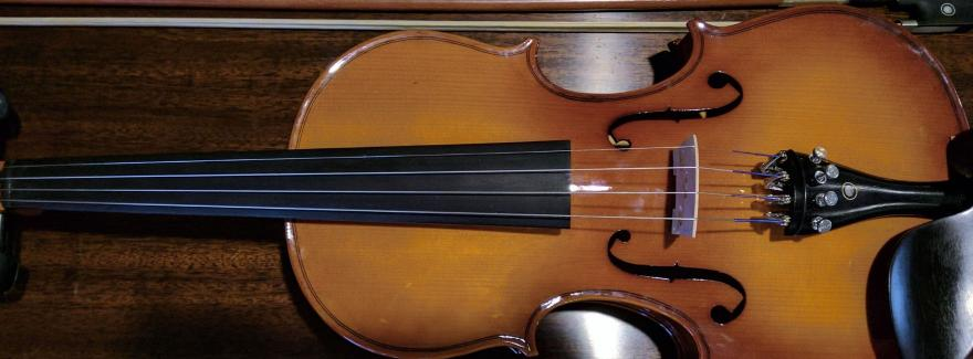 Image of a violin and bow on a dark background