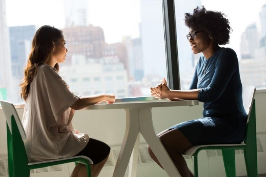 Two women sitting at a table in front of a window, conducting an interview
